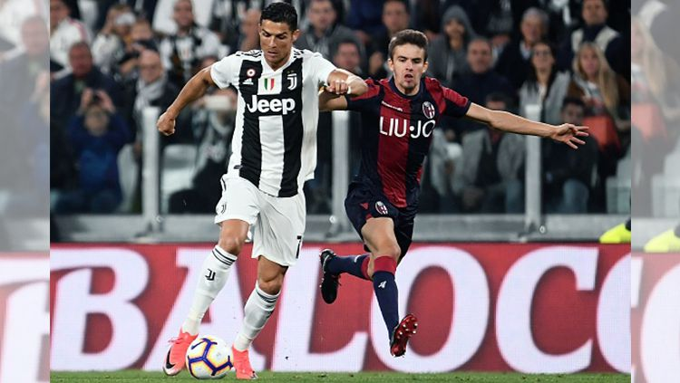Cristiano Ronaldo saat dihalangi pemain Bologna. Copyright: © Getty Images