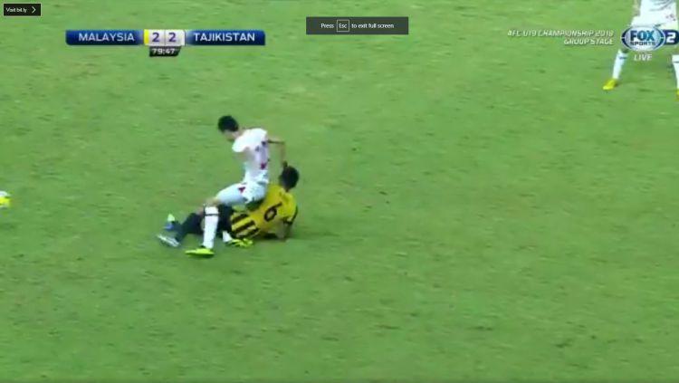 Pemain Malaysia Nabil Hakim saat melakukan tekel ke Khuseyn Nurmatov. Copyright: © afc