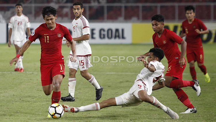 Firza Andika saat menghindari adangan pemain UEA U-19. Copyright: © Herry Ibrahim/INDOSPORT