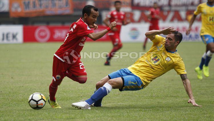 Riko Simanjuntak menghindari jegalan dari pemain Barito Putera. Copyright: © Herry Ibrahim/INDOSPORT