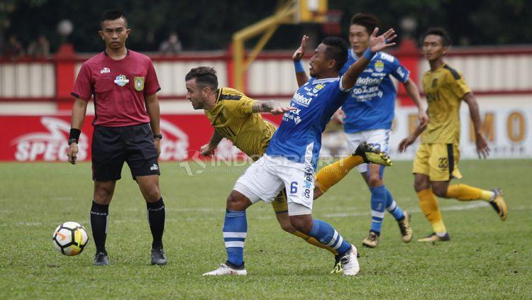 Tony Sucipto berhasil menghentikan aksi pemain Bhayangkara FC. Copyright: © Herry Ibrahim/INDOSPORT