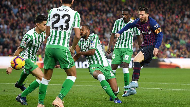 Di tengah adangan lawan, Lionel Messi melancarkan tendangan ke gawang Real Betis. Copyright: © Alex Caparros/Getty Images
