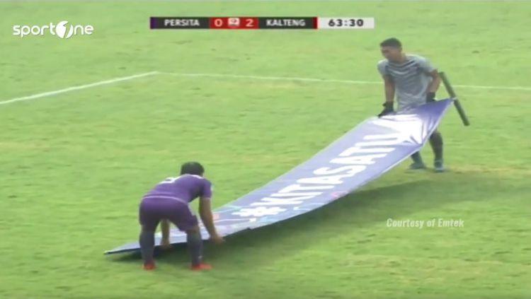 Pemain Persita Tangerang angkat papan iklan. Copyright: © Youtube