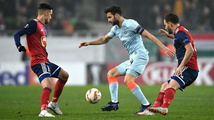 Cecs Fabregas sedang melindungi bola dari rebutan para pemain Vidi FC. Copyright: © Getty Images