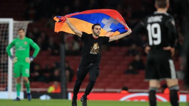 Seorang pria menerobos masuk ke lapangan saat laga Arsenal vs Qarabag Copyright: © Getty Images