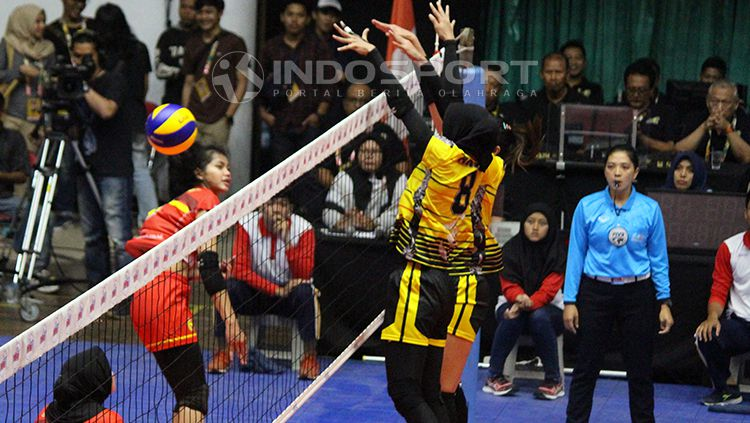 Pemain Jakarta PGN Popsivo memblok smash keras pemain Bandung BJB Pakuan Kokram Pimpichaya. Copyright: © Fitra Herdian/INDOSPORT