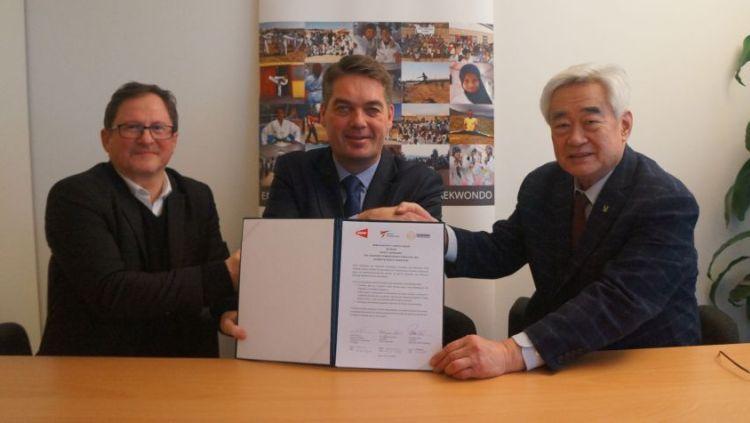 Poul-Erik Hoyer (tengah) saat menandatangani kesepakatan kerja sama dengan taekwondo. Copyright: © Around the rings