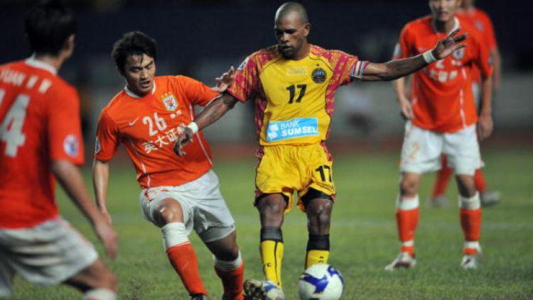 Keith Kayamba Gumbs (kuning) saat melawan Shandong Luneng. Copyright: © INDOSPORT