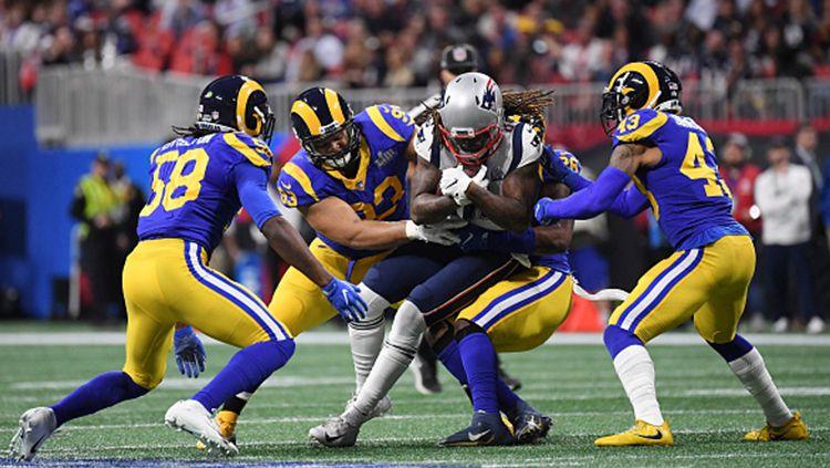 Cordarrelle Patterson (jersey putih) dipaksa empat pemain Los Angeles Rams untuk mengeluarkan bola dari genggamanya Copyright: © GettyImages