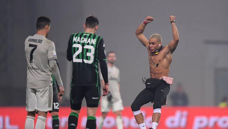 Cristiano Ronaldo dipeluk suporter yang masuk ke lapangan pada saat melawan Sassuolo Copyright: © Getty Images