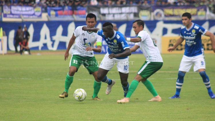 Ezechiel N'Douassel melewati dua pemain Persiwa. Copyright: © Arif Rahman/Indosport.com