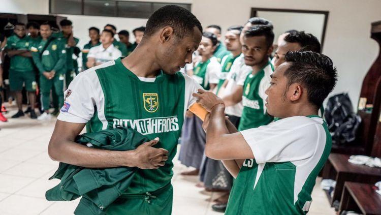 Rendi Irwan menyematkan ban kapten ke Ruben Sanadi. Copyright: © Persebaya.co.id