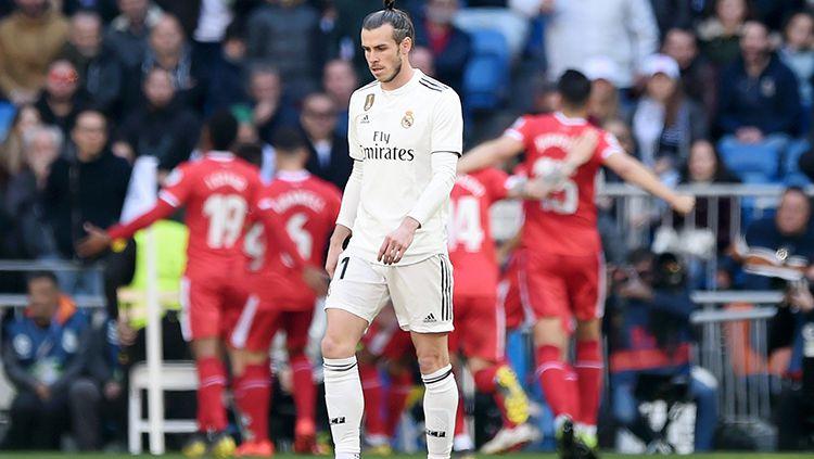Gareth Bale tertunduk lesu dengan background para pemain Girona merayakan gol Copyright: © GettyImages