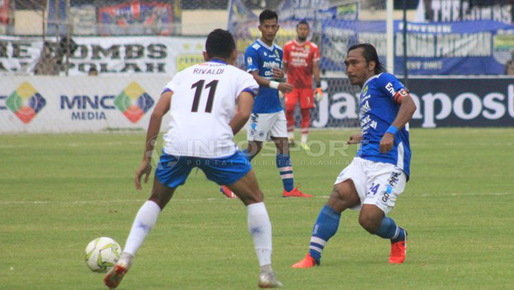 Kapten Persib, Hariono mencoba melewati pemain Arema FC, Rivaldi Copyright: © Arif Rahman/INDOSPORT