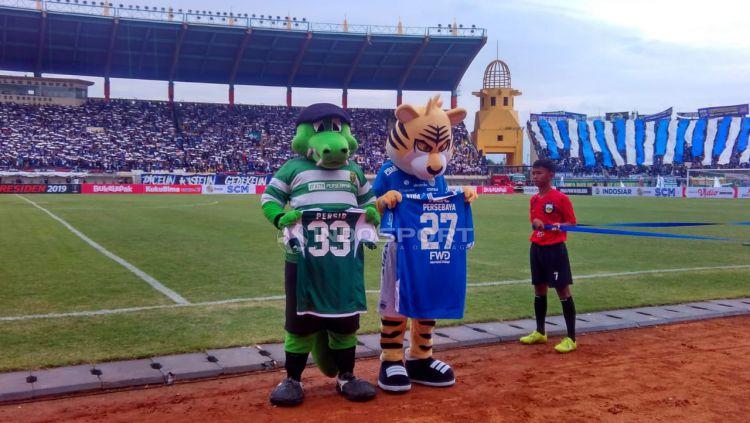 Maskot Persebaya, Jojo, dan maskot Persib, Prabu, bertukar jersey. Copyright: © Arif Rahman/Indosport.com