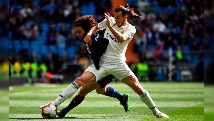 Gareth Bale dihadang pemain lawan pada pertandingan Real Madrid vs Eibar di LaLiga Spanyol, Sabtu (06/04/19). Copyright: © Twitter/@OptaJose