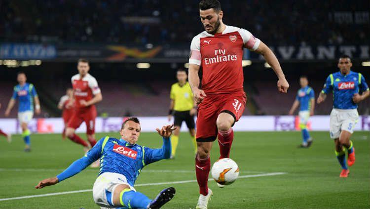 Salah satu pemain Napoli sedang melakukan tekel kepada pemain Arsenal untuk merebut bola. Copyright: © Stuart Franklin/Getty Images