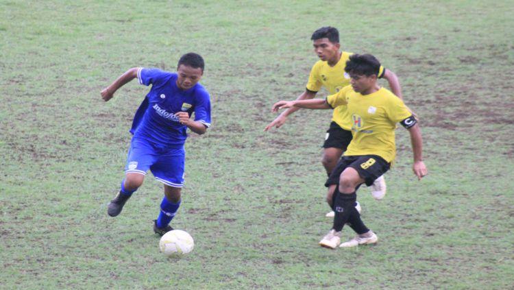 Pemain Persib U-16 dihadang dua pemain Barito Putera U-16 di laga Liga 1 U-16 2019 di Stadion Sport Jabar Arcamanik. Copyright: © INDOSPORT/Arif Rahman