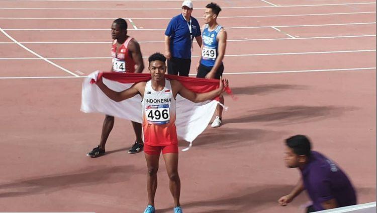 Sprinter Indonesia, Lalu Muhammad Zohri mengibarkan bendera Indonesia usai meraih perak di Kejuaraan Asia 2019 yang digelar di Qatar. Copyright: © Instagram.com/pasipusat