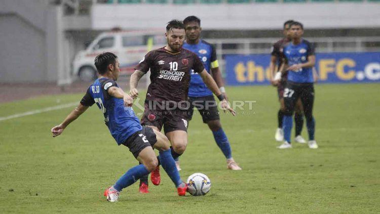 Marc Klok berusaha mengambil bola dari salah satu pemain Home United. Herry Ibrahim/INDOSPORT Copyright: © Herry Ibrahim/INDOSPORT