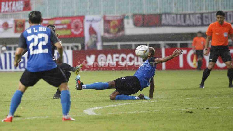 Salah satu pemain Home United menahan tendangan dari Guy Junior. Herry Ibrahim/INDOSPORT Copyright: © Herry Ibrahim/INDOSPORT