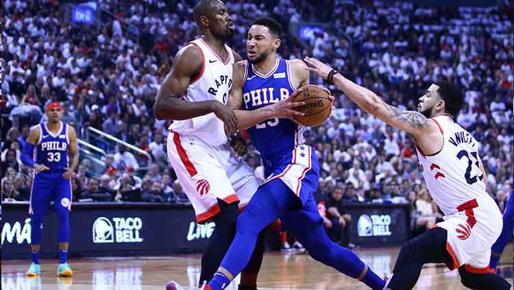 Bintang tim basket Philadelphia 76ers, Ben Simmons mencoba mendribel bola melewati hadangan pemain Toronto Raptors. Copyright: © Vaughn Ridley/Getty Images