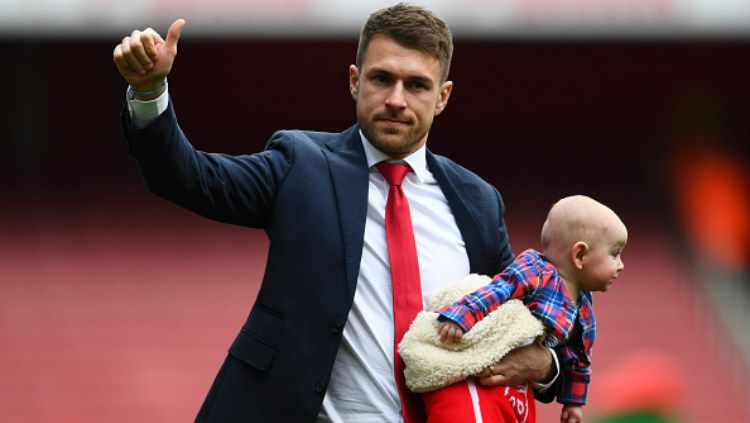 Aaron Ramsey menggendong putranya saat berpamitan usai laga Arsenal vs Brighton di Emirates Stadion, Minggu (05/05/19). Copyright: © Clive Mason/Getty Images