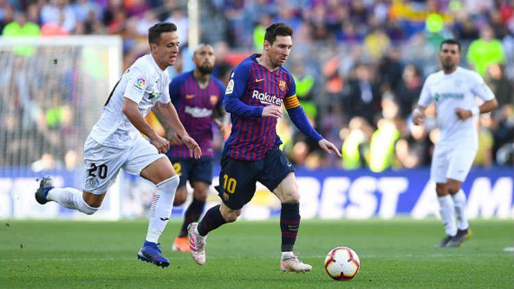 Lionel Messi saat membawa bola dan berusaha direbut oleh para pemain Getafe. Copyright: © Alex Caparros/Getty Images