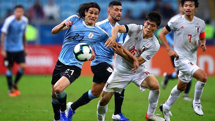 Edinson Cavani dan Takehiro Tomiyasu  di laga Uruguay vs Jepang pada turnamen Copa America 2019, Jumat (21/06/19) Copyright: © Chris Brunskill/Fantasista/Getty Images