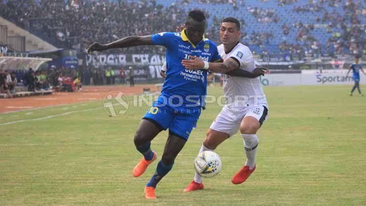 Striker Persib Bandung, Ezechiel NDouassel berduel dengan pemain Madura United di Stadion Si Jalak Harupat, Kabupaten Bandung, Minggu (23/06/2019). Foto: Arif Rahman/INDOSPORT Copyright: © Arif Rahman/INDOSPORT