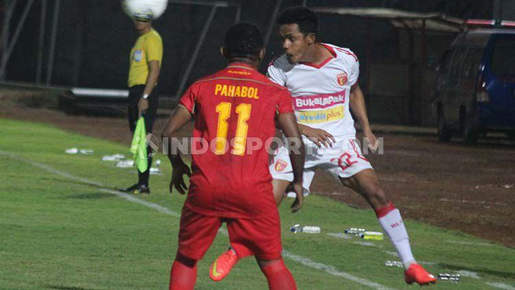 Indosport - Gelandang Badak Lampung FC, Abdulrahman Lestaluhu (kanan) berebut bola dengan winger Kalteng Putra, Ferinando Pahabol dalam laga Liga 1 di Stadion Sultan Agung, Bantul.