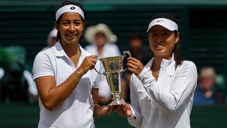 Tami Grende dan Qiu Yu Ye, memegang trofi girl's doubles di Wimbledon 2014 Copyright: © EMPICS Sport - EMPICS / Contributor via Getty Images