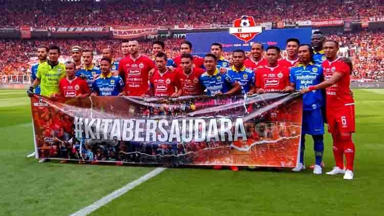 Para pemain Persija Jakarta dan Persib Bandung membentangkan spanduk #KitaBersaudara sebelum pertandingan. Copyright: © Arif Rahman/INDOSPORT