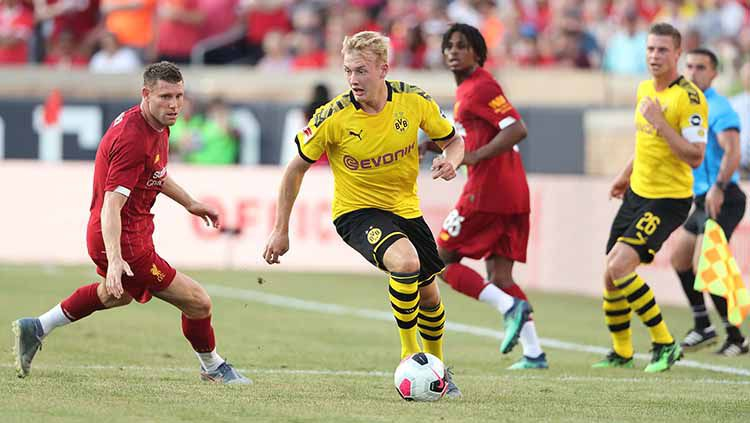 Julian Brandt tengah membawa bola dalam pengawasan James Milner. Copyright: © Matthew Ashton - AMA/Getty Images)