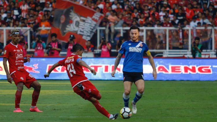 Gelandang PSM Makassar, Marc Klok (biru), mencoba merebut bola dari bek sayap Persija Jakarta, Ismed Sofyan (oranye). Copyright: © Official PSM Makassar