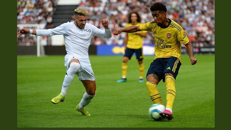 Pemain Arsenal, Reis Nelson, berusaha melewati pemain Angers Copyright: © arsenal.com
