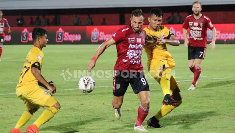 Dua pemain Semen Padang menghalau Spasojevic untuk merebut bola. Copyright: © Nofik Lukman Hakim/INDOSPORT