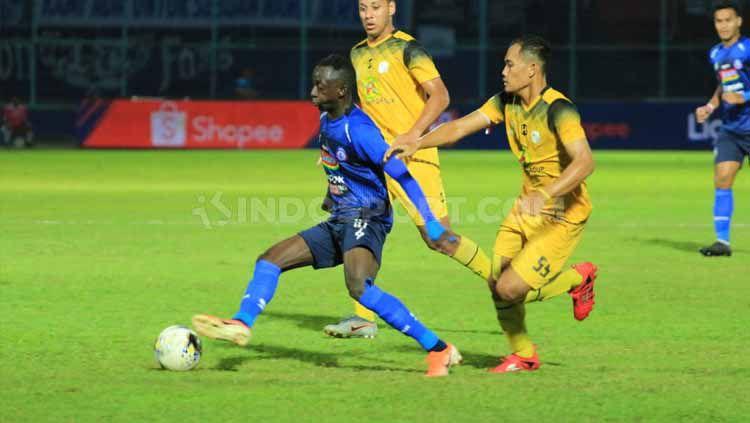 Gelandang andalan Arema FC, Konate Makan sampai dibayangi dua pemain Barito Putera, Senin (19/08/2019) pada pertandingan lanjutan Liga 1 2019. Copyright: © Ian Setiawan/INDOSPORT