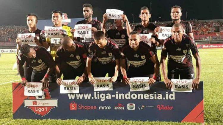 Indosport - Skuat Persipura Jayapura saat membentangkan kertas bertuliskan pesan penolakan terhadap rasisme.