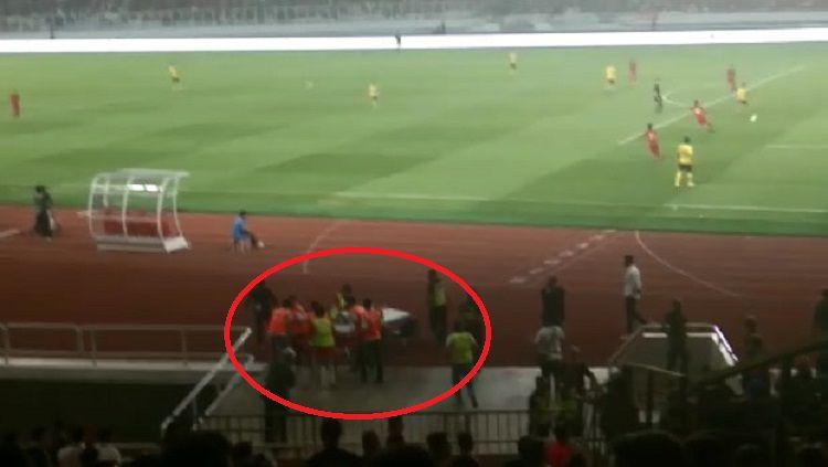 Seorang terduga suporter Malaysia harus ditandu oleh medis usai jadi korban kericuhan di dalam stadion pada laga Timnas Indonesia vs Malaysia, Kamis (05/09/19). Copyright: © Zainal Hasan/INDOSPORT