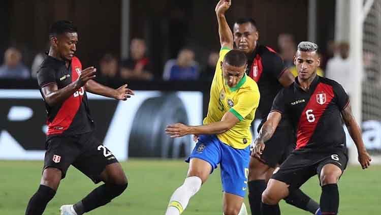 Richarlison berada di antara penjagaan ketat pemain Peru. Copyright: © Twitter.com/brasil