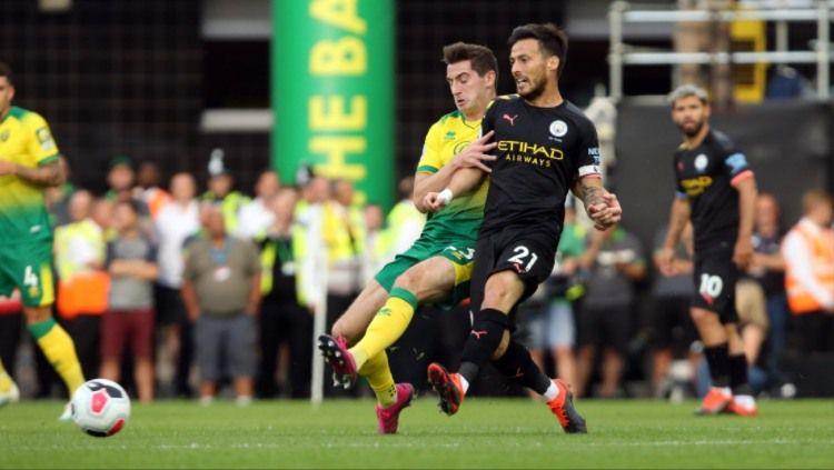 David Silva tengah mengoper bola di laga Norwich vs Manchester City, Sabtu (14/09/19). Copyright: © Norwich