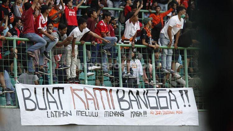 Indosport - Suporter Persija Jakarta memberikan dukungan pada pemain Persija Jakarta pada pertandingan Liga 1 di Stadion Patriot Bekasi, Minggu (15/09/19).