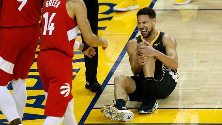 Bintang Golden State Warriors, Klay Thompson, mengerang kesakitan setelah mendapat cedera pada partai final NBA 2018-2019 menghadapi Toronto Raptors. Copyright: © Lachlan Cunningham/Getty Images