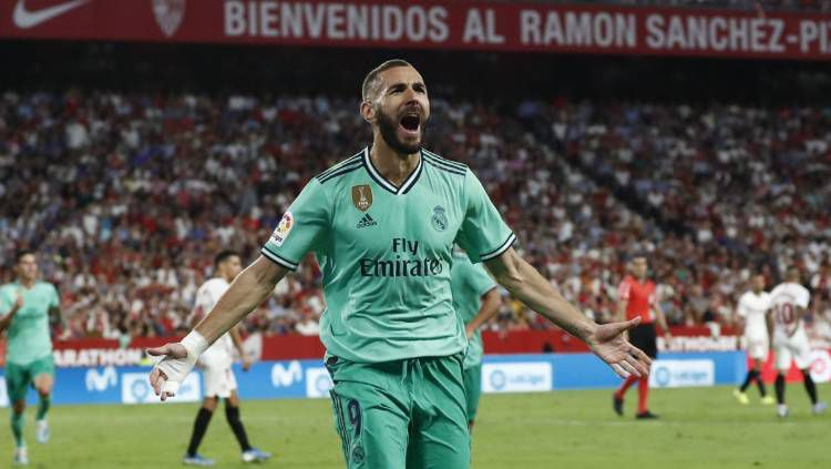 Striker Real Madrid, Karim Benzema, merayakan golnya ke gawang Sevilla dalam lanjutan Liga Spanyol 2019/20. Copyright: © Twitter @realmadrid