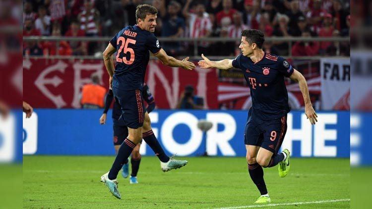 Thomas Mueller (kiri) jabat tangan dengan Robert Lewandowski (kanan) pada laga Olympiakos vs Bayern Munchen di Liga Champions 2019/2020, Rabu (23/10/19). Copyright: © Twitter/@SuperSportTV