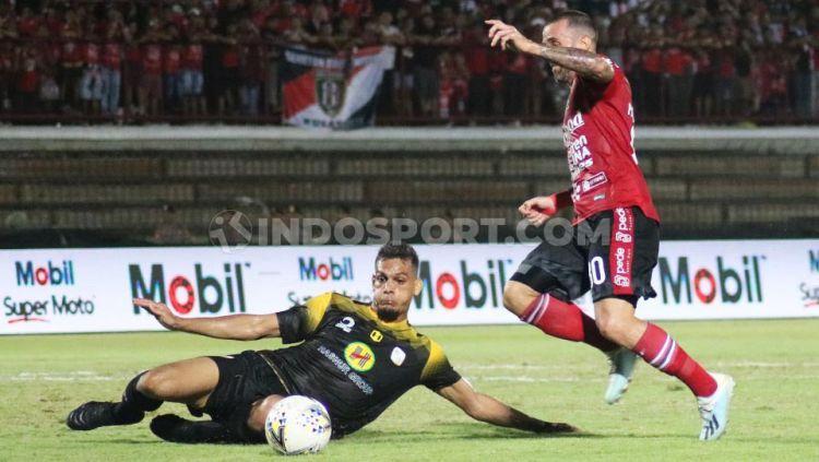 Bek Barito Putera, Cassio De Jesus berusaha membuang bola yang hendak direbut gelandang Bali United, Paulo Sergio dalam lanjutan Shopee Liga 1 2019 di Stadion Kapten I Wayan Dipta, Gianyar, Minggu (27/10/19). Copyright: © Nofik Lukman Hakim/INDOSPORT