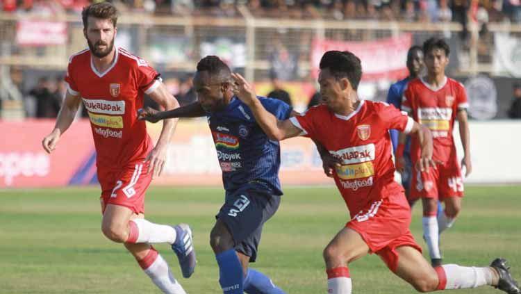 Dua pemain Badak Lampung FC tengan berduel dengan Ricky Kayame Copyright: © aremafcofficial