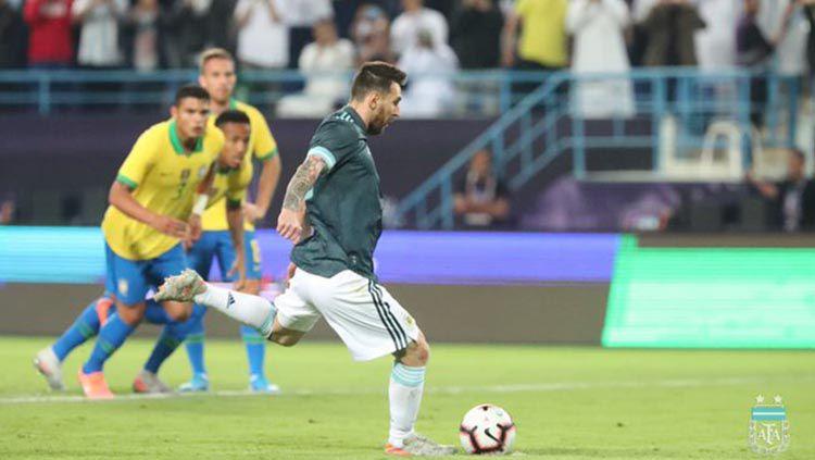 Lionel Messi saat melakukan tendangan penalti melawan Brasil di laga uji coba. Copyright: © Twitter.com/@Argentina