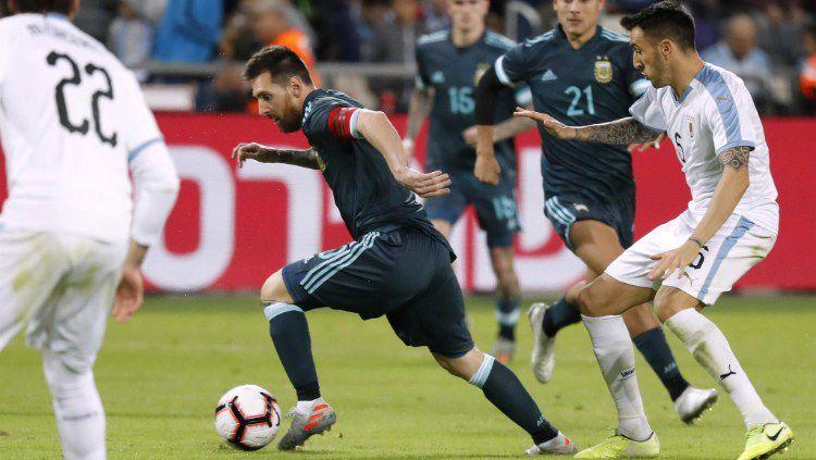 Lionel Messi saat dijaga oleh bek lawan dalam pertandingan persahabatan Argentina vs Uruguay, Selasa (19/11/19) dini hari WIB. Copyright: © afa.com.ar